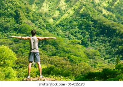 Fit male doing stretching exercise against a beautiful nature setting