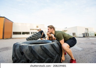 Fit male and female athletes doing tire-flip exercise outdoors