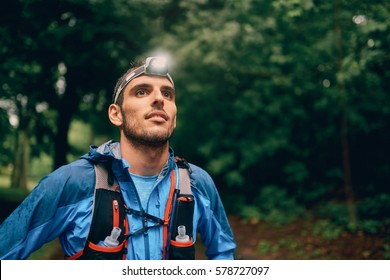Fit male jogger with a headlamp rests during training for cross country trail race in nature park.