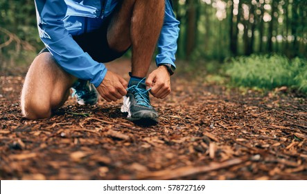 Fit male jogger ties shoes while day training for cross country forest trail race in a nature park.