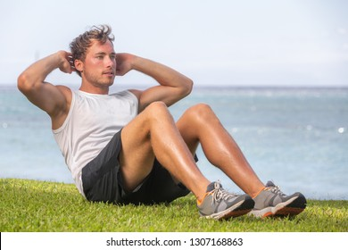 Fit man athlete training outside on grass doing situps for abs workout fat belly weight loss. Healthy active lifestyle.