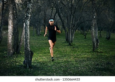 Fit man with beard running fast on the forest