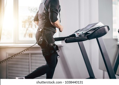 Fit Man in black suit for ems training preparing for running on treadmill at gym