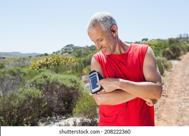 Fit man changing the song on his music player on mountain trail on a sunny day