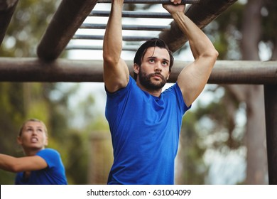 Fit man climbing monkey bars in bootcamp