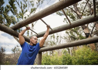 Fit man climbing monkey bars during obstacle course in boot camp