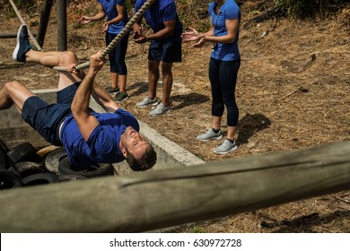 Fit man crossing the rope during obstacle course while people cheering him