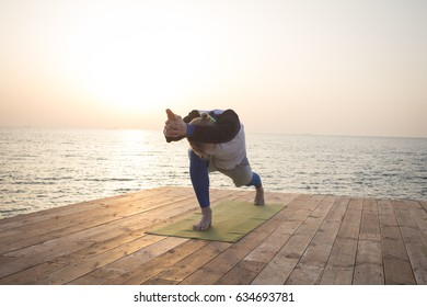fit man do yoga asana on the wooden pier in the morning