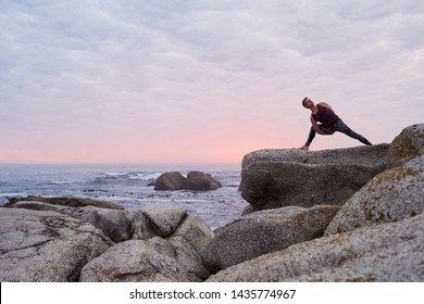 Fit man doing the eight angle pose while practicing yoga on some rocks by the ocean against a dramatic sky at dusk