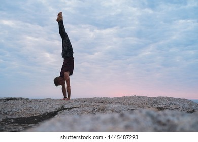 Fit man doing a hand stand while practicing yoga on a rock by the ocean against a dramatic sky at dusk