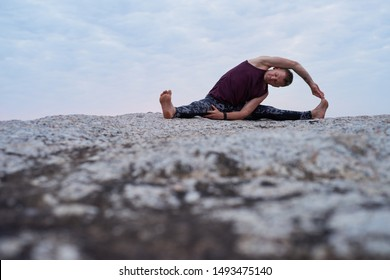 Fit man doing the revolved head to knee pose while practicing yoga on a rock by the ocean against a dramatic sky at dusk