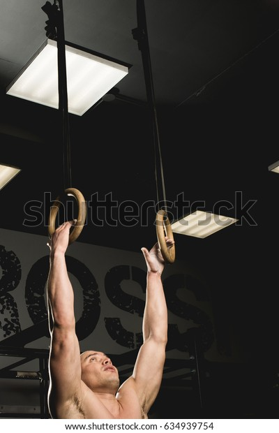 A fit man doing some dips on exercise rings