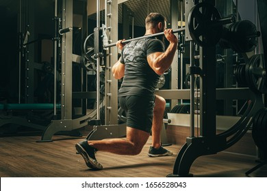 Fit man doing squats in a training machine