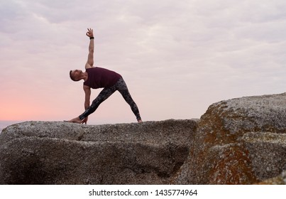 Fit man doing the triangle pose while practicing yoga on some rocks by the ocean against a dramatic sky at dusk