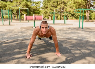 Fit man exercising at the park, leading a healthy life.Muscular young man during his workout on the street. Fit, fitness, workout, exercise, dips and healthy lifestyle concept.