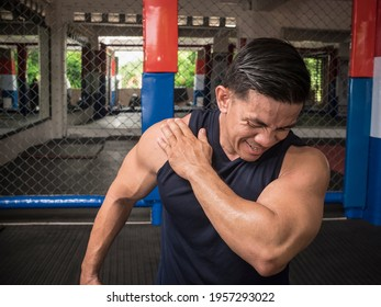 A fit man experiences rotator cuff tear, sprain or injury during a workout session at the gym.