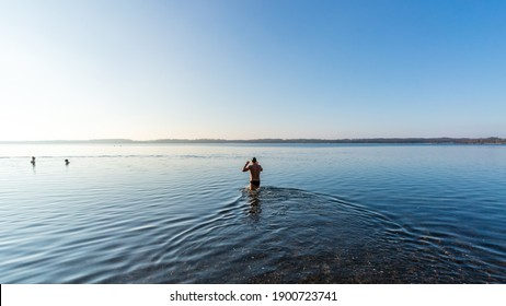 Fit man goes into a lake to swim