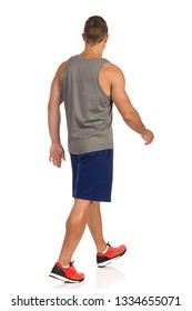 Fit man in gray tank top, blue shorts and orange sneakers is walking and looking away. Rear side view. Full length studio shot isolated on white.