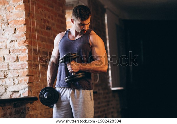 Fit man at the gym with dumbbell
