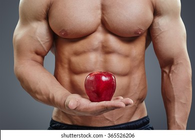 Fit man holding a fresh red apple on grey background. Healthy food abstract concept. Shirtless bodybuilder with perfect six pack abs healthy diet concept.