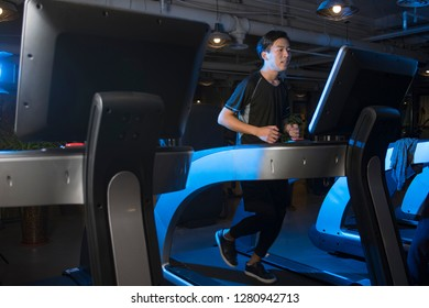 Fit man jogging on the treadmill at the gym