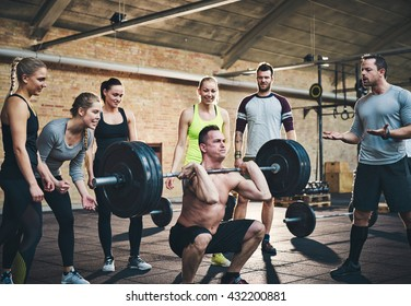 Fit man lifting barbells looking focused, working out in a gym with other people cheering him on in support