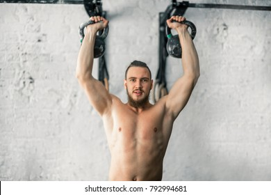 fit man lifting two kettlebell workout exercise at gym.