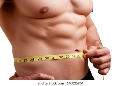 Fit man measuring his waist after a workout in the gym, isolated in a white background