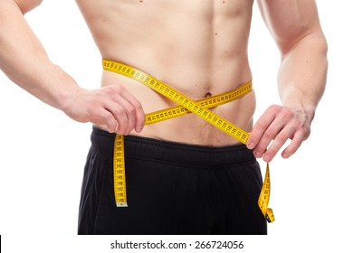 Fit man measuring his waist after a workout in the gym, isolated in a white background.