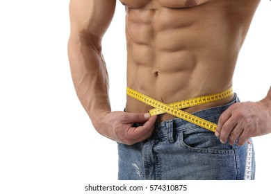 Fit man measuring his waist in front of white background