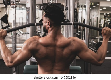 Fit man on lat pulldown machine at the health club. Work out on Pulldown Weight Machine
