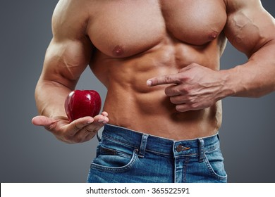 Fit man pointing to fresh red apple. Healthy vegetarian nutrition concept. Muscular bodybuilder with six pack abs holding apple.