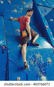 Fit man rock climbing indoors at the gym