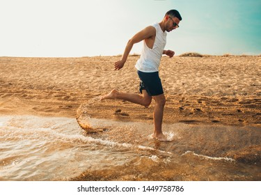 Fit man run in the sea with world map made of clouds. Concept of summertime