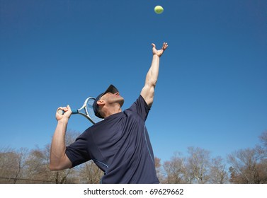 Fit man serving tennis ball serve outside
