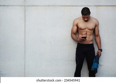 Fit man with sexy abdominal using mobile phone taking a break after workout outdoors, attractive dark skinned man in sportswear resting after run using smart phone