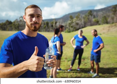 Fit man showing thumbs up while holding water bottle in boot camp