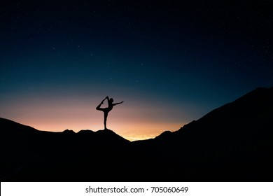 Fit Man in silhouette doing yoga natarajasana pose at night city and starry sky background