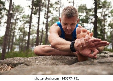 Fit man sitting on a rocky outcrop doing the head to knee pose while practicing yoga alone in a pine forest