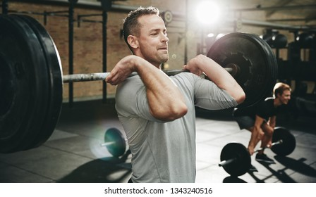 Fit man in sportswear focused on lifting weights during a strength training session at the gym