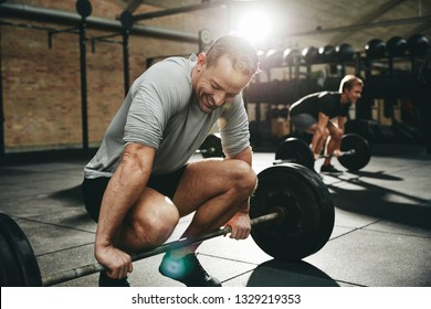 Fit man in sportswear laughing while trying to lift a barbell with heavy weights during a workout session at the gym