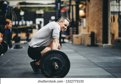 Fit man in sportswear smiling while preparing to lift heavy weights during a workout session at the gym