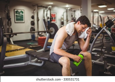 Fit man taking a break from working out at the gym
