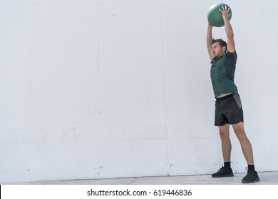 Fit man throwing medicine ball doing ball slam against gym floor or shoulder press upper body workout exercise. Cross training at fitness center.