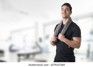 Fit man with a towel around his neck, in a gym