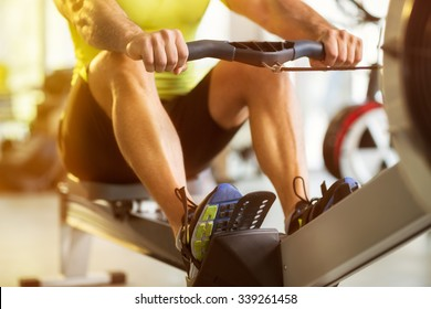 Fit man training on row machine in gym