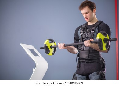 Fit Man wearing black electrostimulation suit lifting barbell closeup, power pose