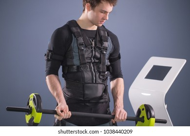 Fit Man wearing black electrostimulation suit lifting barbell closeup, power pose