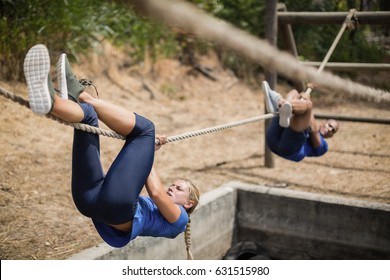 Fit man and woman crossing the rope during obstacle course in boot camp