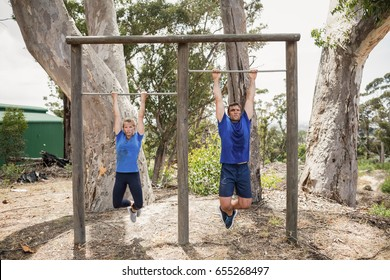Fit man and woman performing pull-ups on bar during obstacle course in boot camp